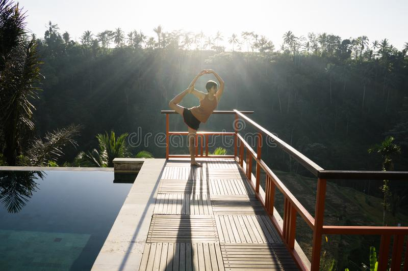 A model of a beautiful, short-haired and young woman doing yoga with Natarajasana poses by the pool with views of rice fields and royalty free stock photos