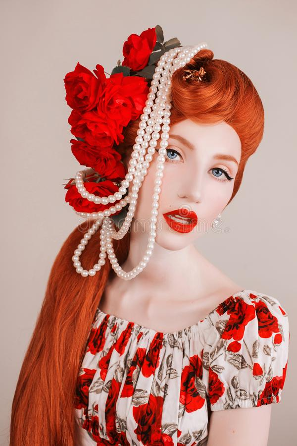 Model with beauty makeup on face. Blue eyes and red lips. White shiny beads. Long red hair. Redhead model with flower hairstyle on stock photos