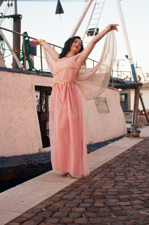 Model bij het overzees in de winter, met het lange roze kleding glimlachen stock foto's