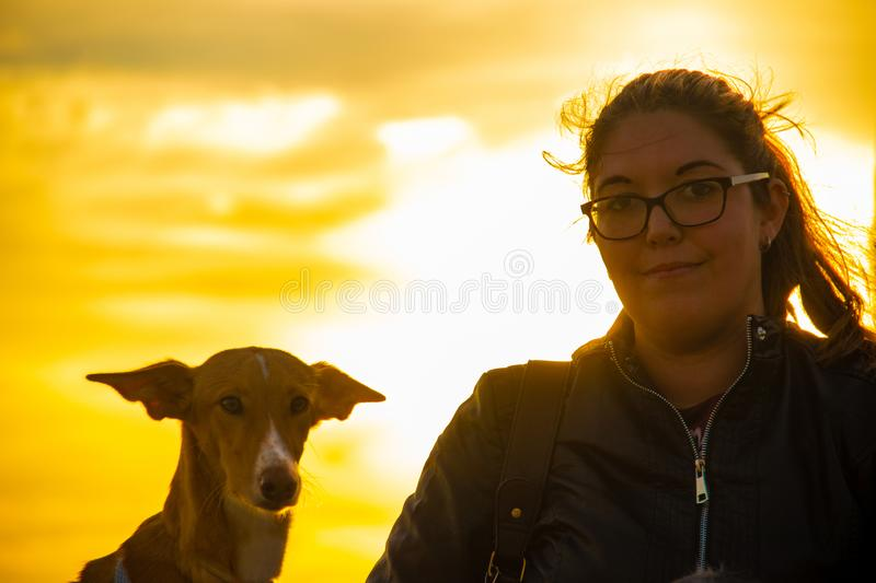 Model with black jacket outdoors in a sunset with pets royalty free stock image