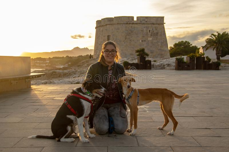 Model with black jacket outdoors in a sunset with pets royalty free stock photography