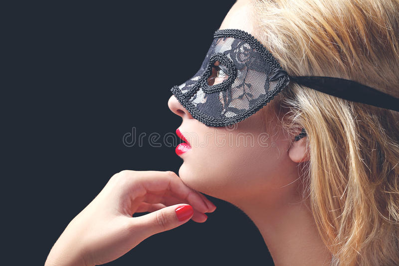Model with black lace mask. Beautiful model with black lace mask, red lips and manicure royalty free stock photos