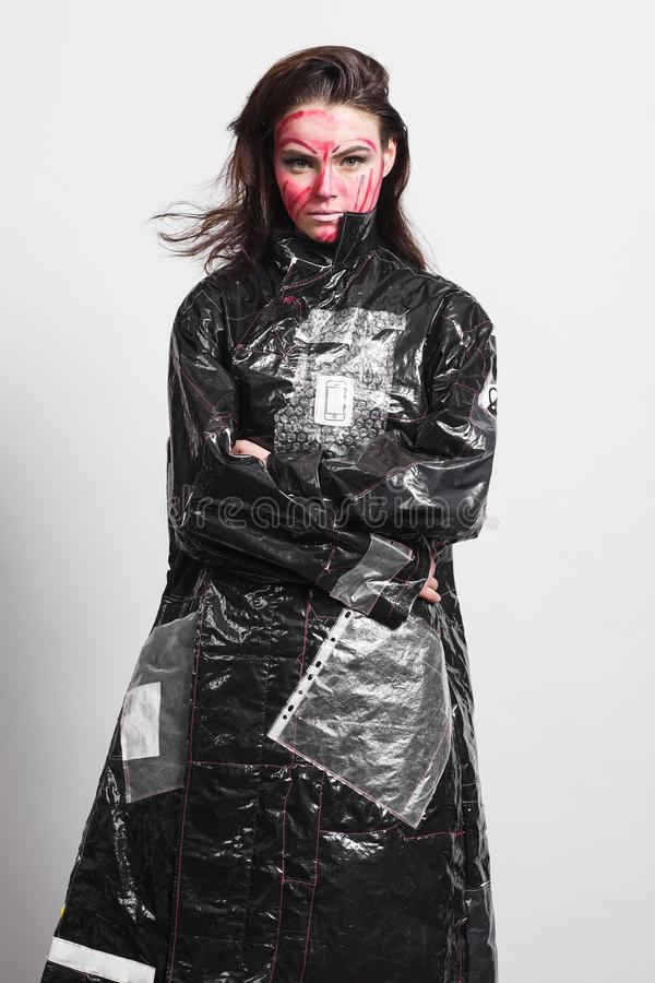 Model in a black raincoat made of cellophane and in creative make-up. Studio photo session. White background stock photos