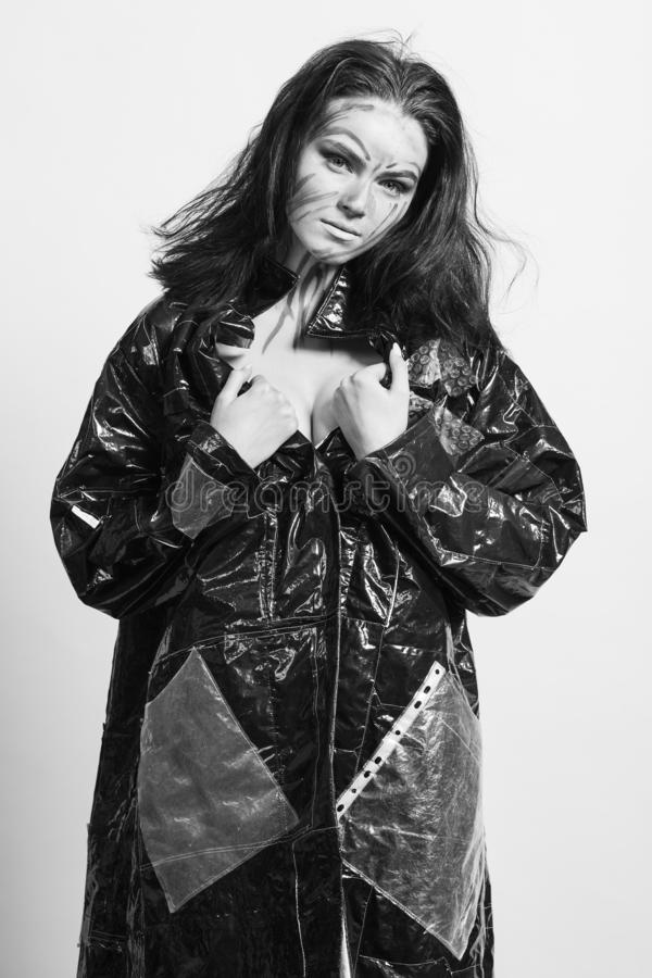 Model in a black raincoat made of cellophane and in creative make-up. Studio photo session. White background stock images