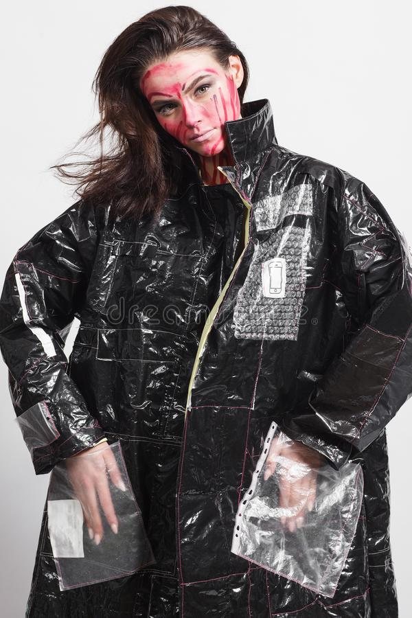 Model in a black raincoat made of cellophane and in creative make-up. Studio photo session. White background royalty free stock photo