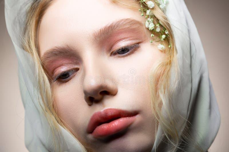 Model with blue eyes and light pink eyeshades posing professionally. Pink eyeshades. Close up of blonde-haired model with blue eyes and light pink eyeshades royalty free stock photo