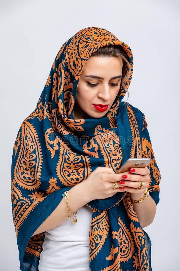 Model with blue kalagai scarf on head with Golden patterns with phone in hands isolated on white background. royalty free stock photo