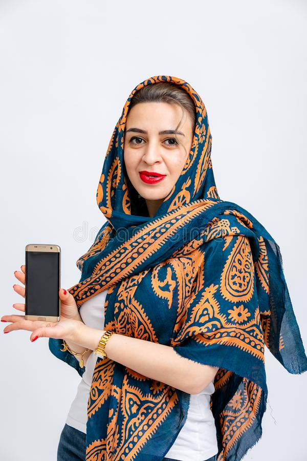 Model with blue kalagai scarf on head with Golden patterns with phone in hands isolated on white background. royalty free stock images