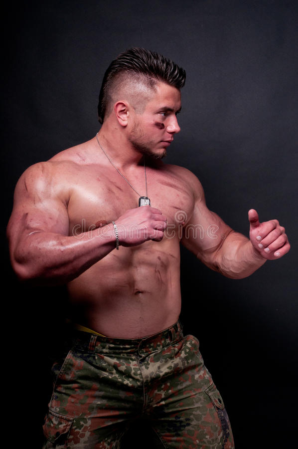 Model in camouflage. Muscled male in camouflage pants royalty free stock photography