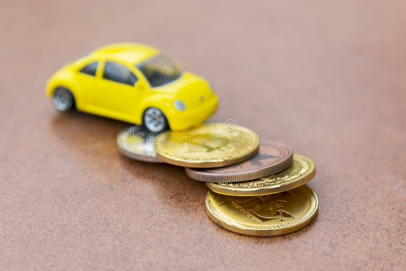 Model of car on background of coins, concept of car loan, car insurance, leasing, transport tax. Model of car on background of coins, concept of car loan, car stock image
