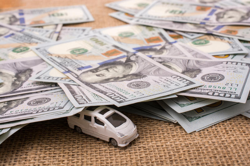 Model car covered by US dollar banknotes. Spread on ground royalty free stock photography