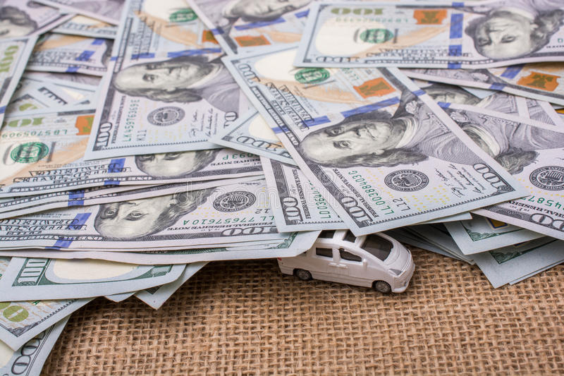 Model car covered by US dollar banknotes. Spread on ground stock photo