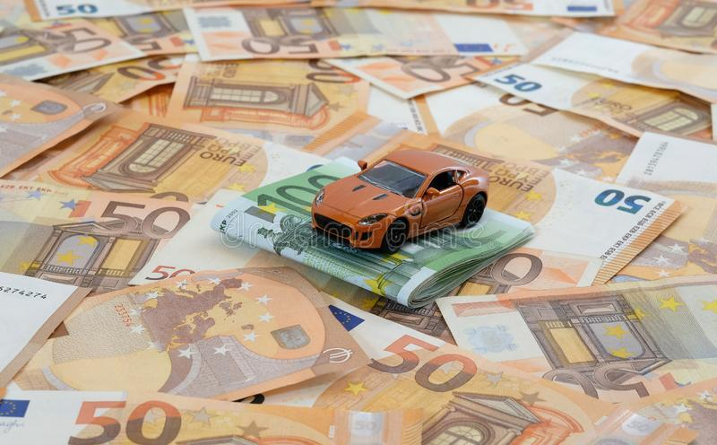 Orange sports car on bills concept car costs. A model car on laid out 50 Euro banknotes with 100 Euro banknotes as concept car costs stock photos