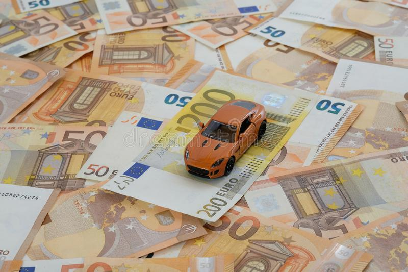 Orange sports car on bills concept car costs. A model car on laid out 50 Euro banknotes with 200 Euro banknote as concept car costs stock photo