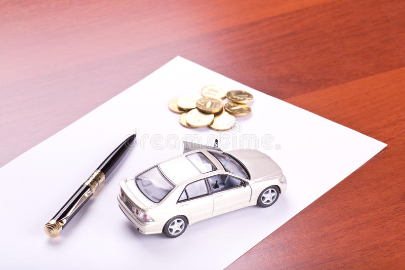 Model of the car, pen and coins. On table royalty free stock photography