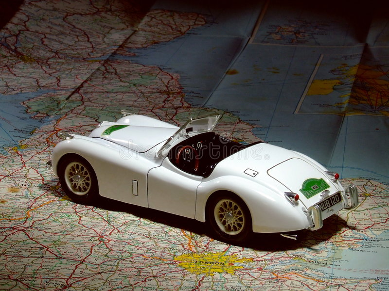 Model Car on Road Map. A scale model of a 1948 Jaguar XK 120 sitting on an old road map of Britain stock photos