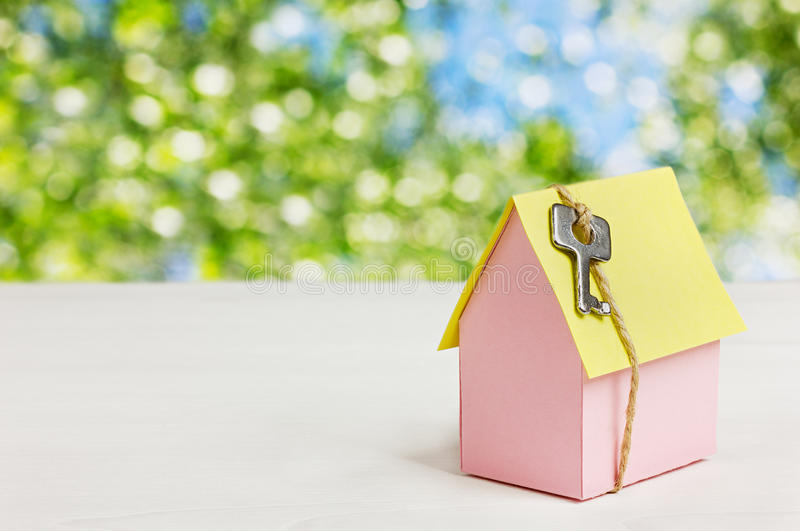 Model of cardboard house with a bow of twine and key against green bokeh background. house building, loan, real estate or buying stock photography