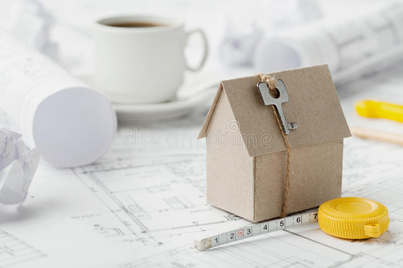 Model cardboard house with key and tape measure on blueprint. Home building, architectural and construction design concept royalty free stock photos