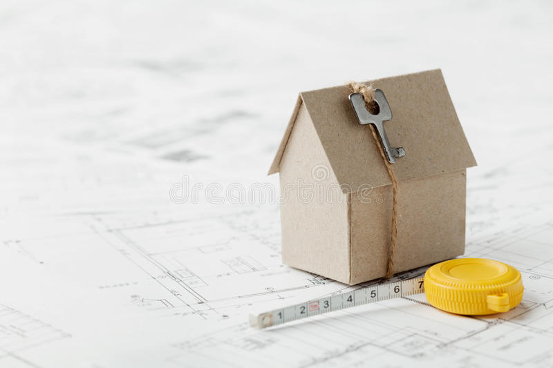 Model cardboard house with key and tape measure on blueprint. Home building, architectural and construction design concept stock photo