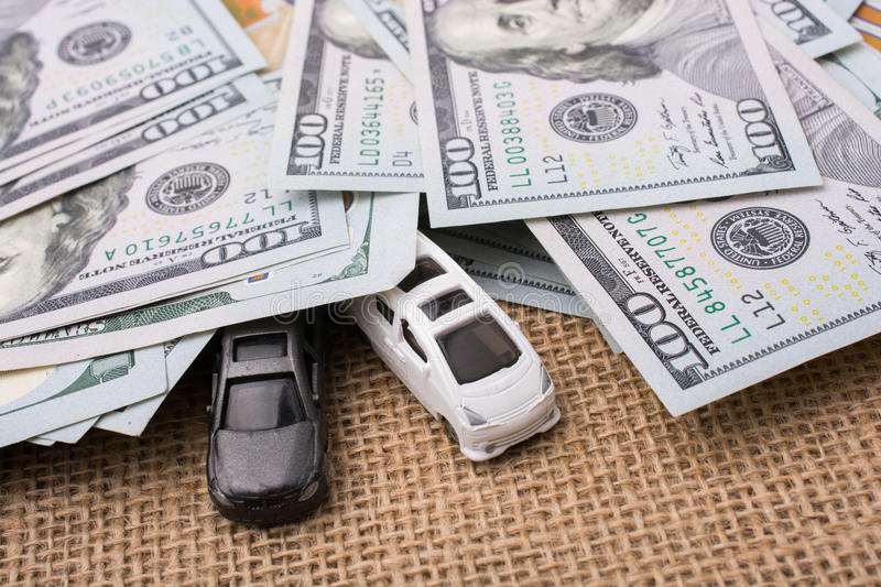 Model cars covered by US dollar banknotes. Spread on ground royalty free stock photo