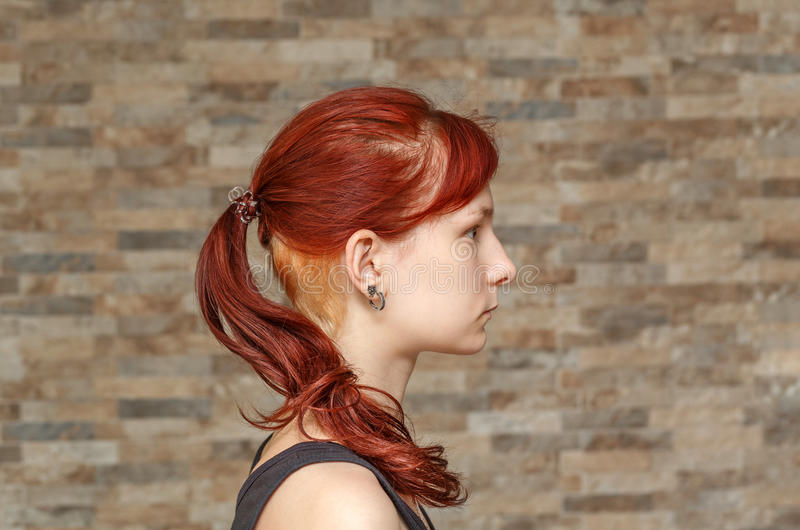 Model with colored tail and hidden undercut. Young model with colored tail and hidden undercut bleached hair royalty free stock photos