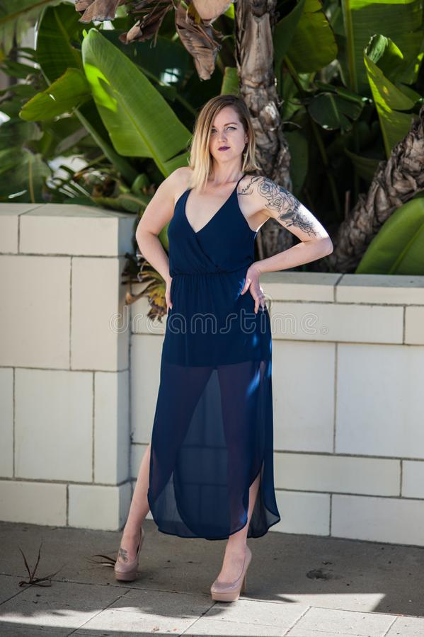 Sassy blonde super model in blue sheer dress. Model with confident attitude posed with hands on hips in front of white brick wall and foliage stock images