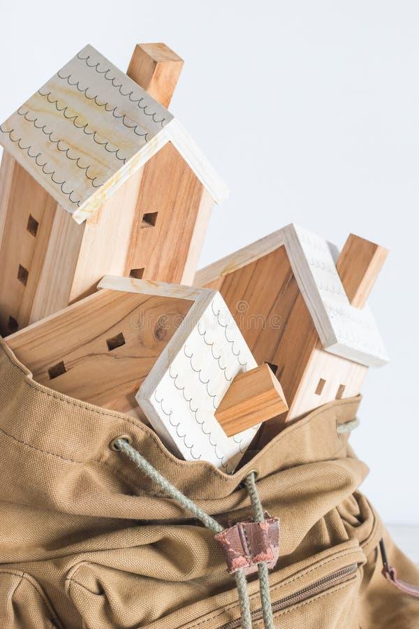 Model domku miniaturowego w brązowym plecaku na białym tle obraz royalty free