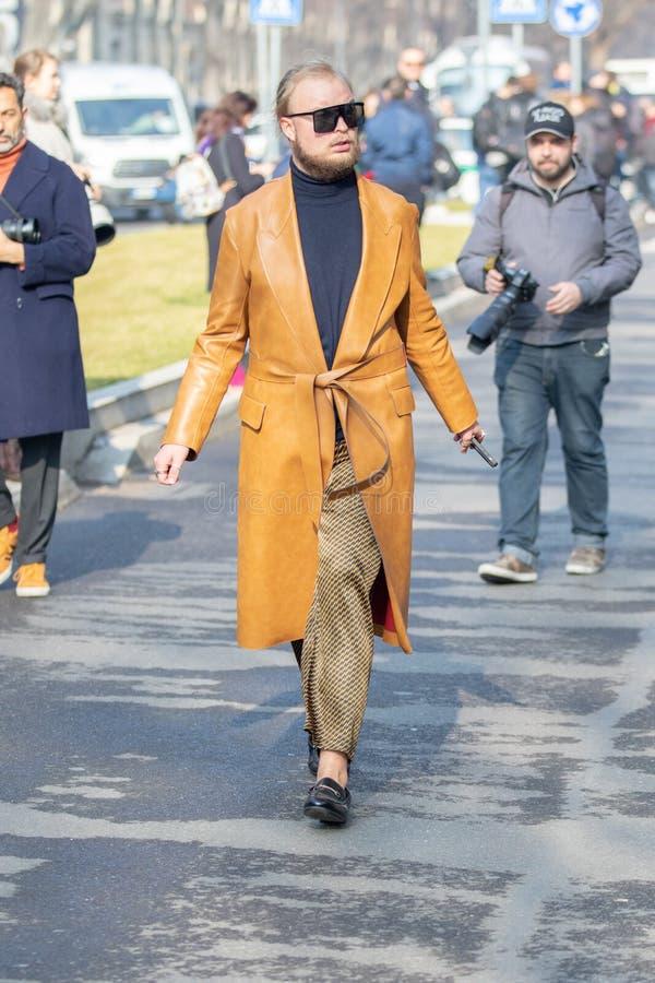 Model dragend een paar bevlekte broek, een paar mocassins zonder sokken en een bruine leeroverjas royalty-vrije stock fotografie
