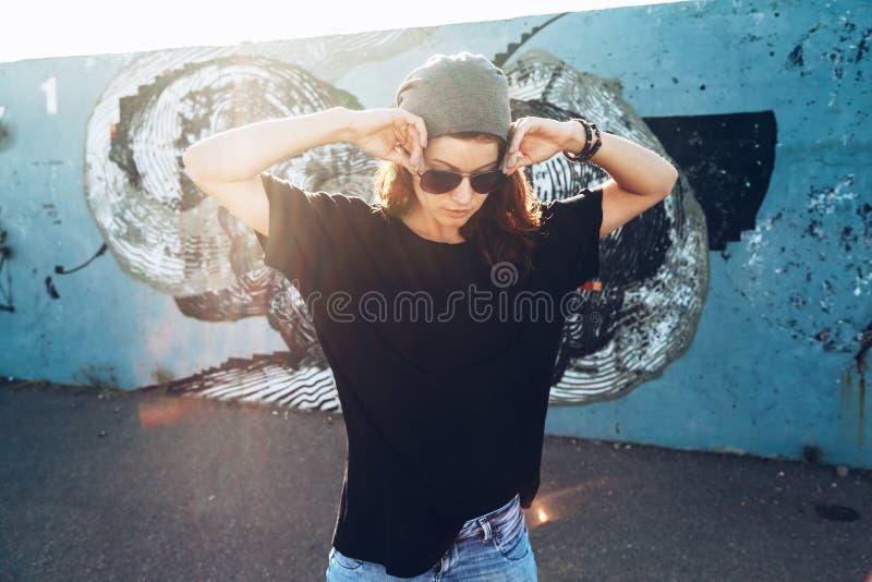 Model dragende duidelijke t-shirt en zonnebril die over straat stellen wal stock foto
