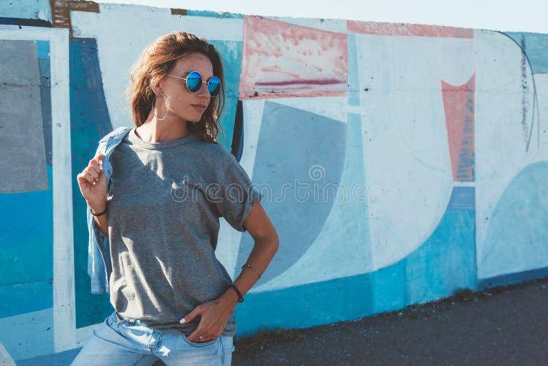 Model dragende duidelijke t-shirt en zonnebril die over straat stellen wal stock afbeeldingen