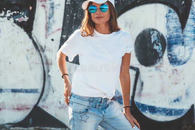 Model dragende duidelijke t-shirt en zonnebril die over straat stellen wal stock foto's