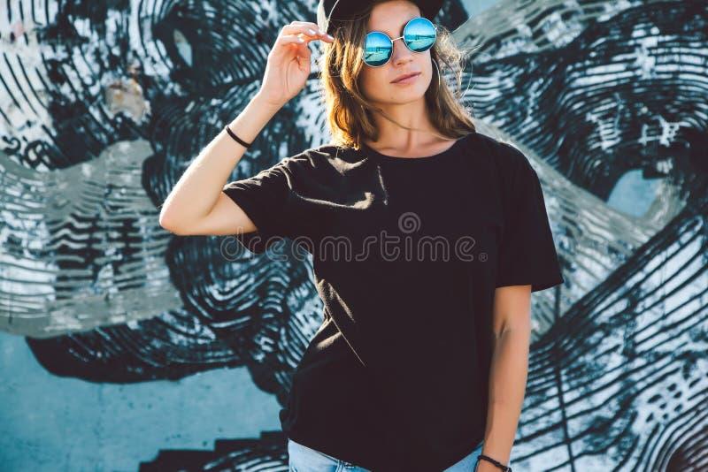 Model dragende duidelijke t-shirt en zonnebril die over straat stellen wal royalty-vrije stock foto