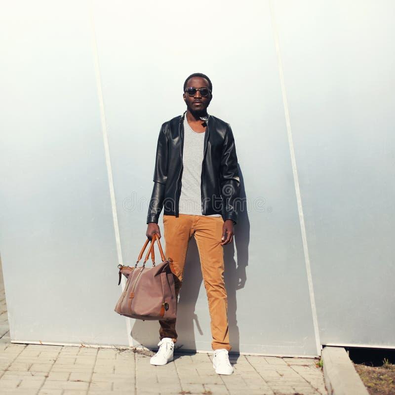 Model dragende zonnebril van de manier de Afrikaanse mens en zwart leerjasje met zak stock foto's
