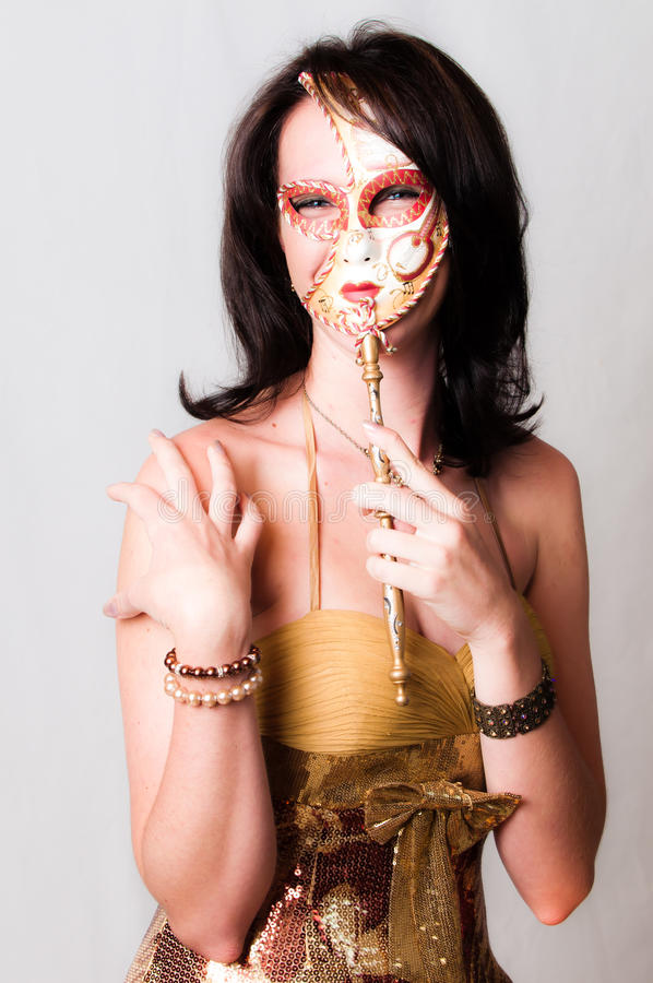 Model dressed in gold with venetian carnival face stock images