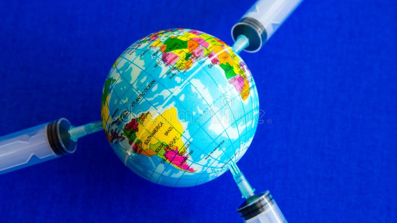 The model earth on the syringe on blue background- image royalty free stock photography