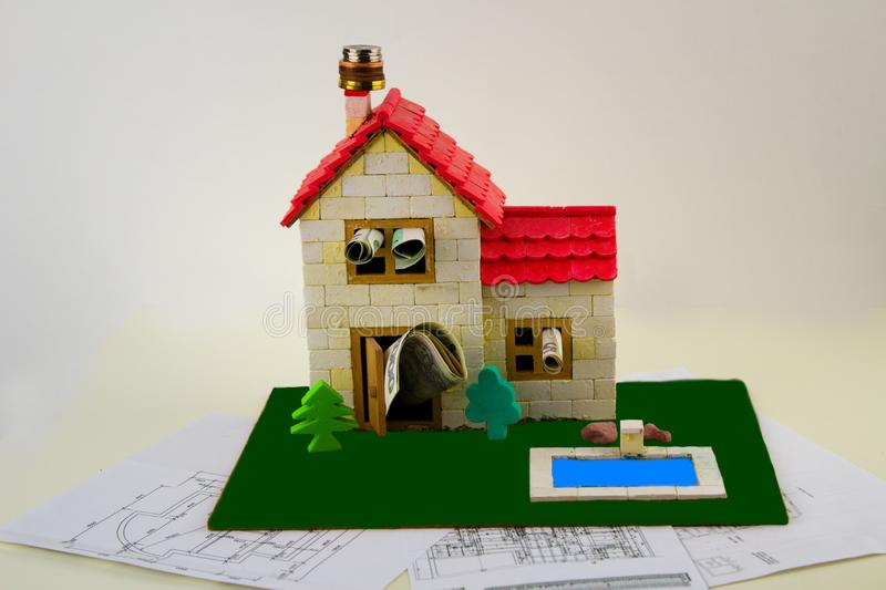 Model of a family house has coins on the chimney, banknotes in windows and stands on building plans. Model family house with swimming pool and garden. The stock photos