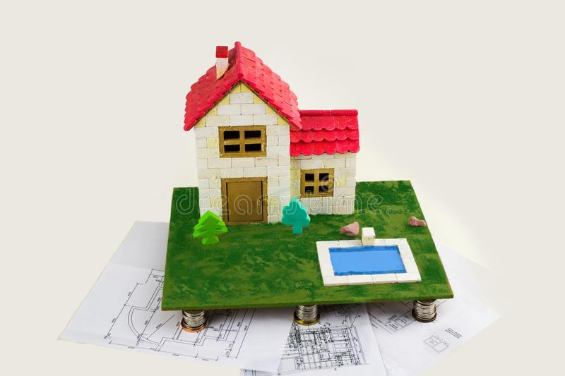 model of a family house stands on pillars of coins and building plans. royalty free stock photography