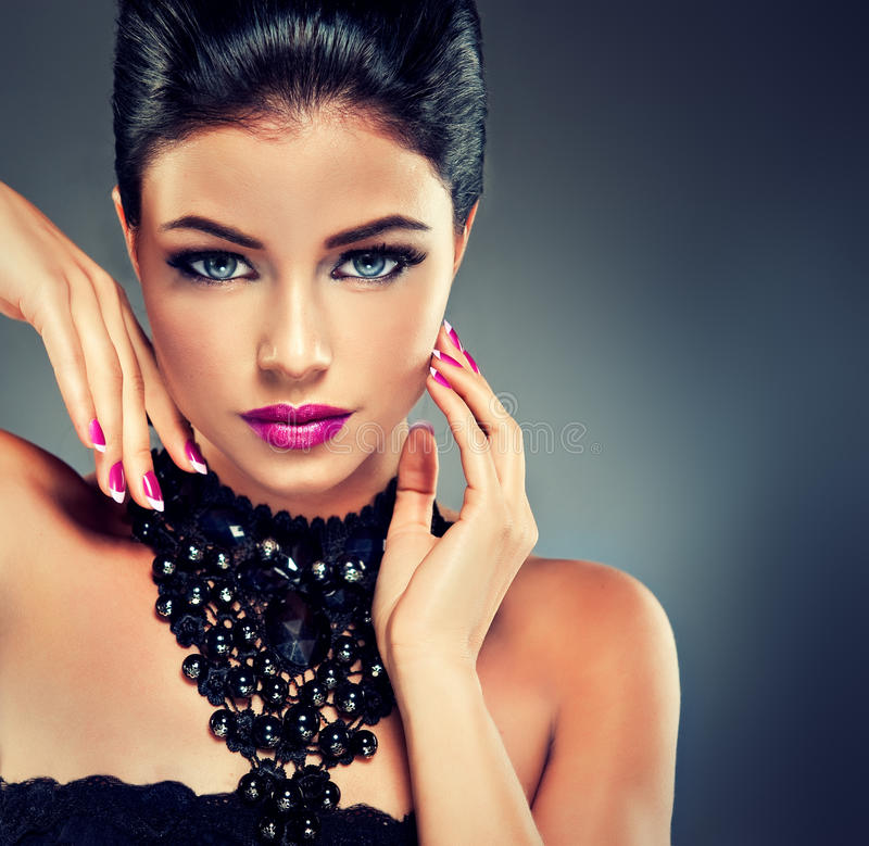 Model with fashionable nail Polish. Fuchsia and black necklace