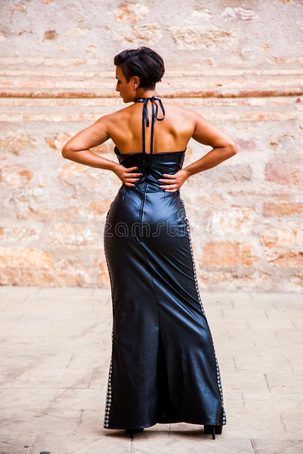 Model female fashion poses back with a long black leather dress stock photo