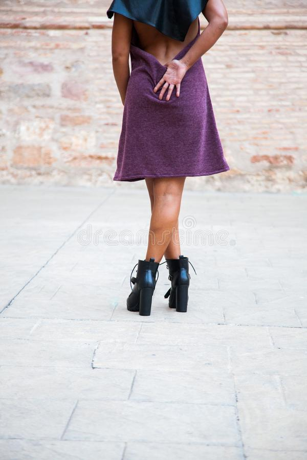 Model of female fashion poses back to camera with a short summer dress, legs crossed and not seen head stock photos