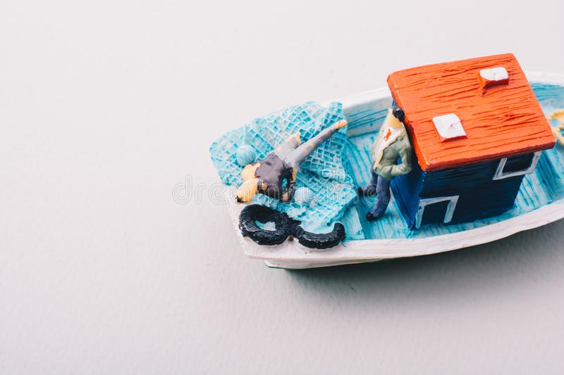 Model fishing boat with a tiny man on board. Little colorful model fishing boat with a tiny man on board stock photography