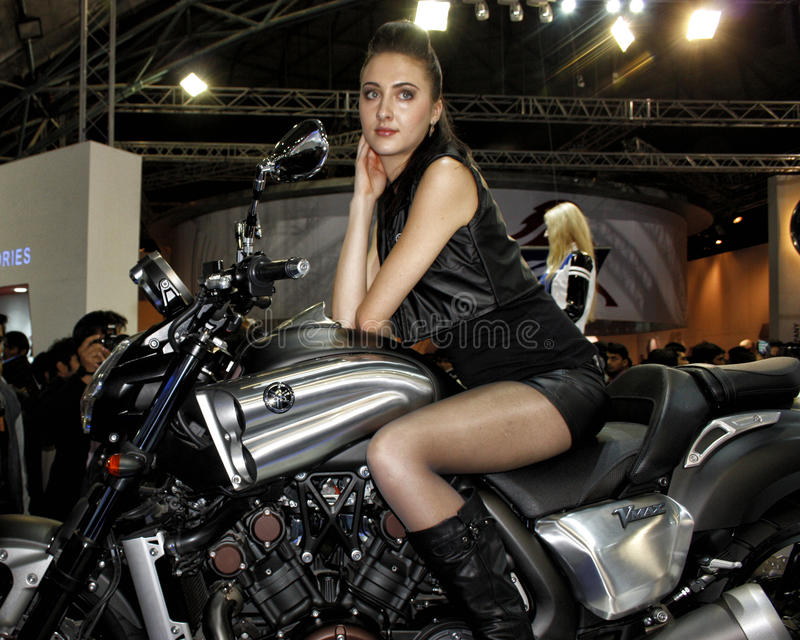 A model flaunts her looks at an event on a super bike. A beautiful young model poses on a super bike with aplomb royalty free stock photo