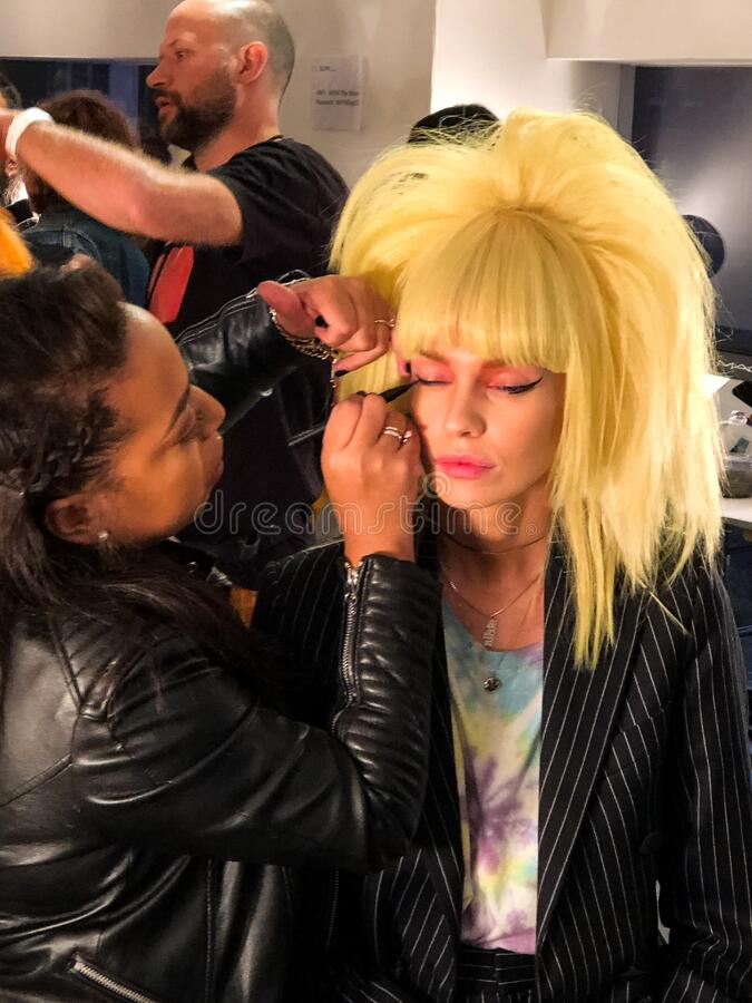 A model getting ready backstage for the Jeremy Scott runway show stock photography