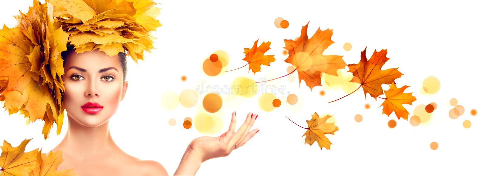 Model girl with autumn bright leaves hairstyle showing copyspace on open hand palm royalty free stock image