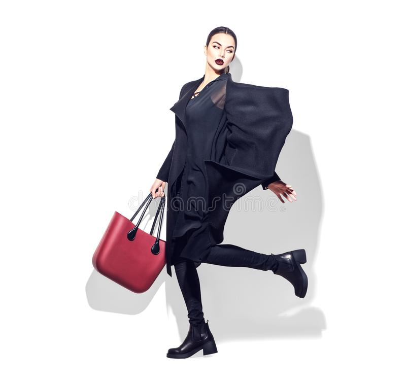 Model girl full length portrait on white background. Woman posing in fashionable clothes in studio. Casual style. Black coat, trendy bag and shoes stock image