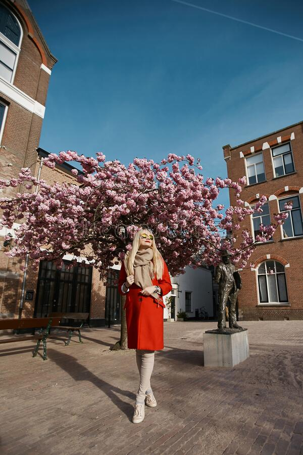 Model girl in red coat standing under pink blossoming tree at the urban background. Fashion concept. Elegant young woman. In trendy outfit and sunglasses royalty free stock photo