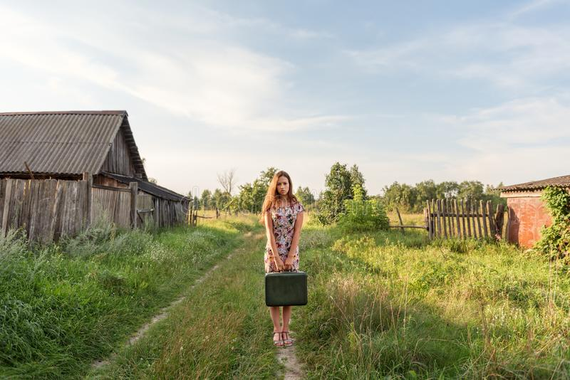 A model girl in a retro dress is holding in her hands a vintage suitcase on an abandoned country road overgrown with grass royalty free stock photo