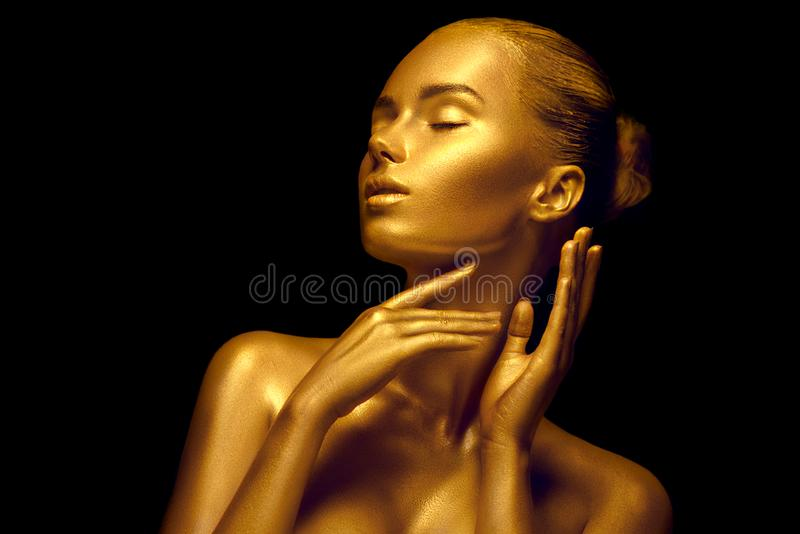 Model girl with shiny golden professional makeup over black. Beauty sexy woman with golden skin. Fashion art portrait closeup. Gold jewellery royalty free stock image