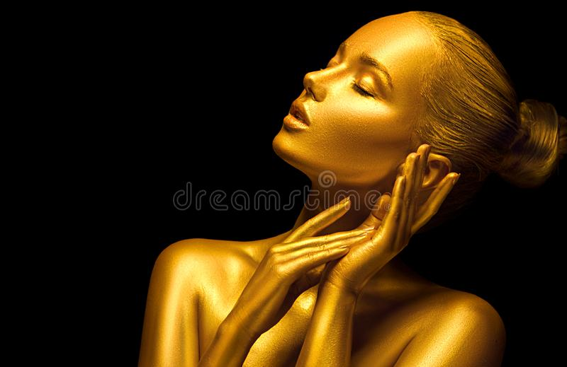 Model girl with shiny golden professional makeup over black. Beauty sexy woman with golden skin. Fashion art portrait closeup. Gold jewellery royalty free stock photography