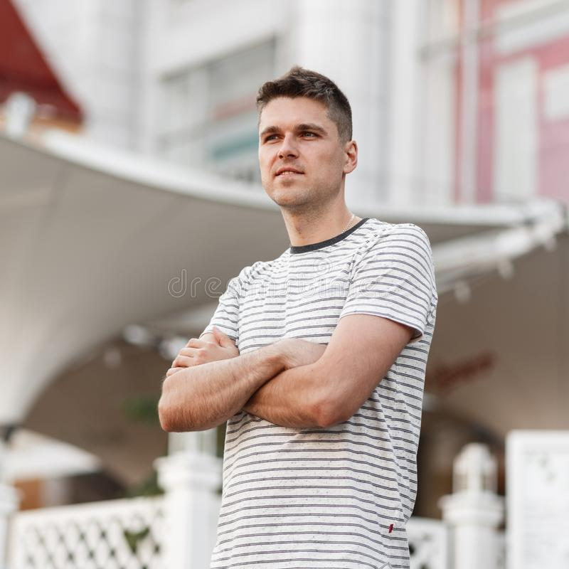Model of a handsome young man with a stylish hairstyle in a fashionable T-shirt posing on a street in the city near a summer cafe stock photo